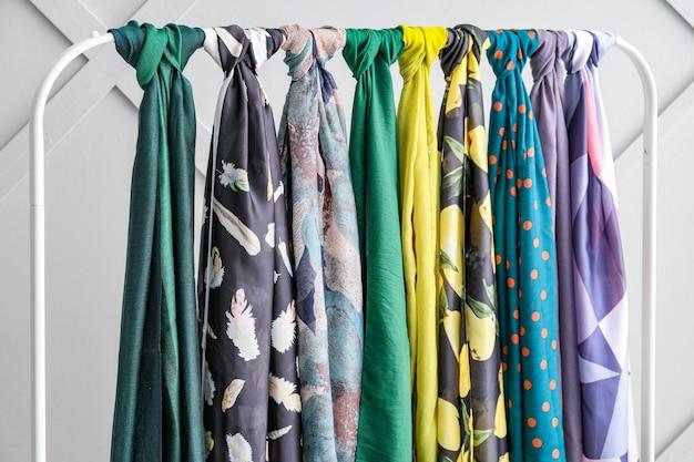 Различные красивые шарфы на стойке