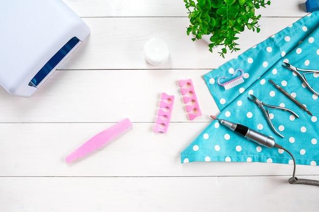 Различная красота и личная гигиена аппаратный педикюр и маникюр ноги, ручные инструменты для ногтей и аксессуары на белом, помещенные на стол. ножницы, кусачки для полировки ногтей кусачки для вросших ногтей