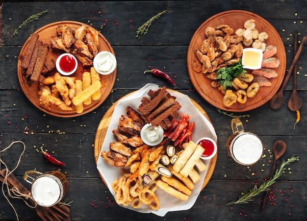 Различные пивные закуски на круглых деревянных досках