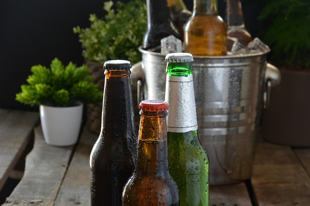 Different beers on a table of wood. there are bottle and glass with ice to keep them cold