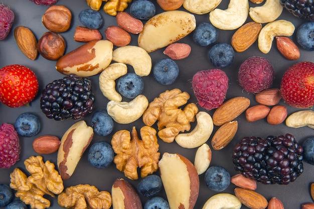 Различные ягоды и орехи на тарелке. здоровая пища фон