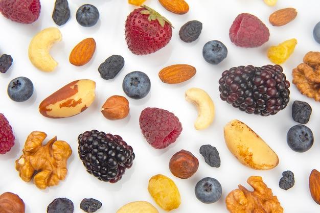 Различные ягоды и орехи на белом фоне. витаминные белки и здоровая пища