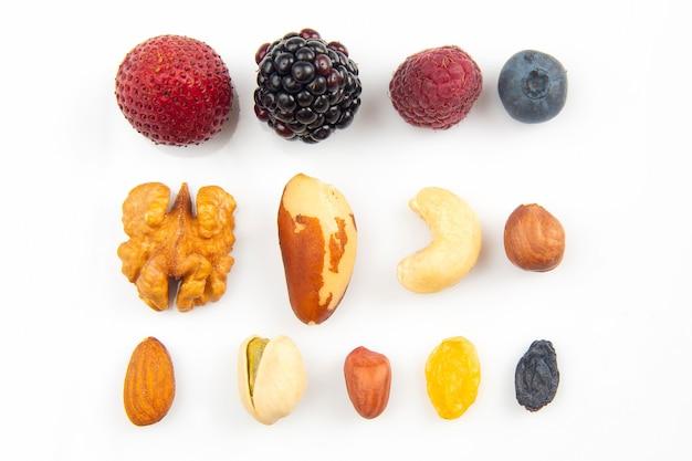 Различные ягоды и орехи на белом