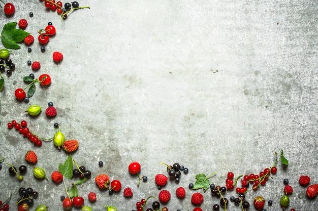 Различные ягоды на старом каменном столе.