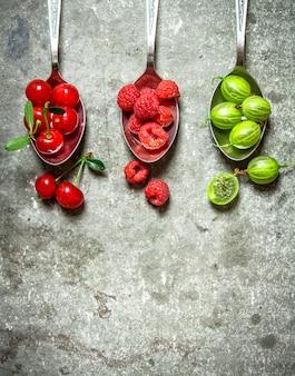 Ложки разных ягод. на каменном столе.