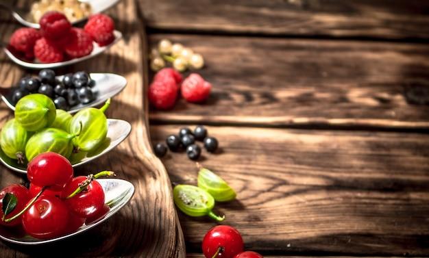 Ложки разных ягод. на деревянном столе.