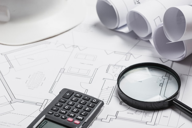 Different blueprints and supplies on office table