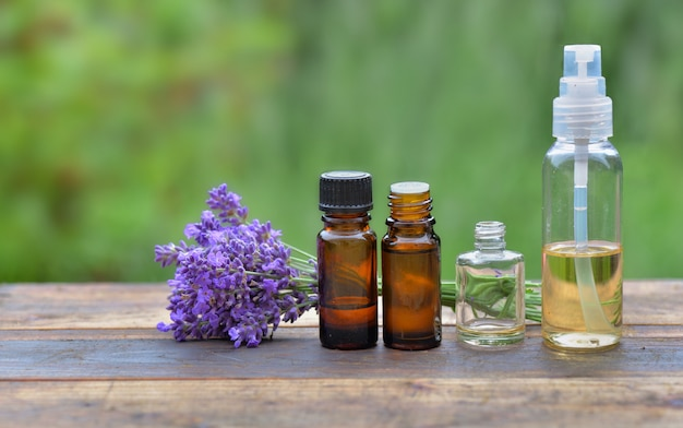 Different  of bottles of essential oil and little bouquet of  lavender flower arranged on a wooden table on green background