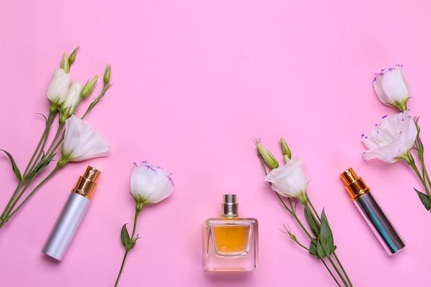 明るいピンクの背景に香水と美しい花のトルコギキョウのさまざまなボトル。女性用アクセサリー。上面図