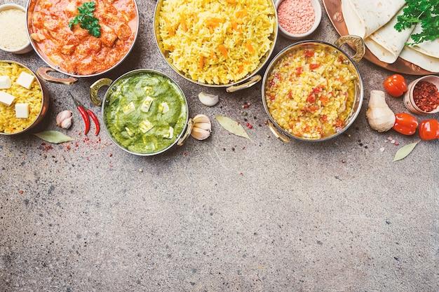 Различные миски с разнообразной индийской едой на серой каменной поверхности, вид сверху.