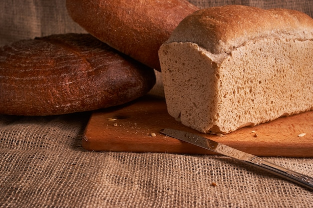 Different bread and wheat on the rustic table.