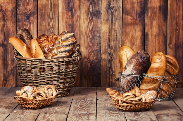 Different bread with ears in basket on wooden background.