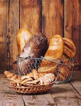 木製の背景にバスケットに耳を持つ別のパン。