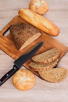Разные породы на деревянных фоне. нож на деревянной доске с хлебом и разными булочками на столе. хрустящий хлеб на деревянной доске.