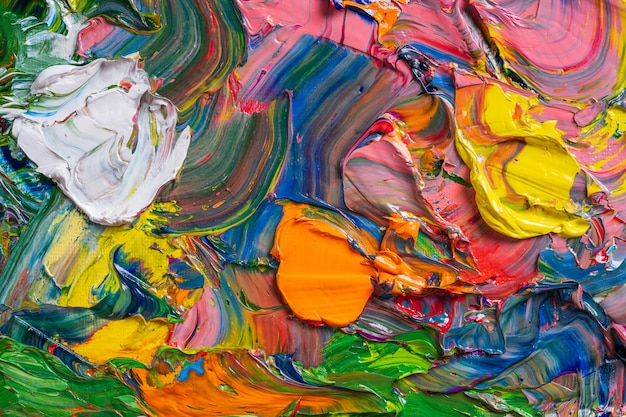 Different bright colors of oil paints are mixed on a palette close-up.