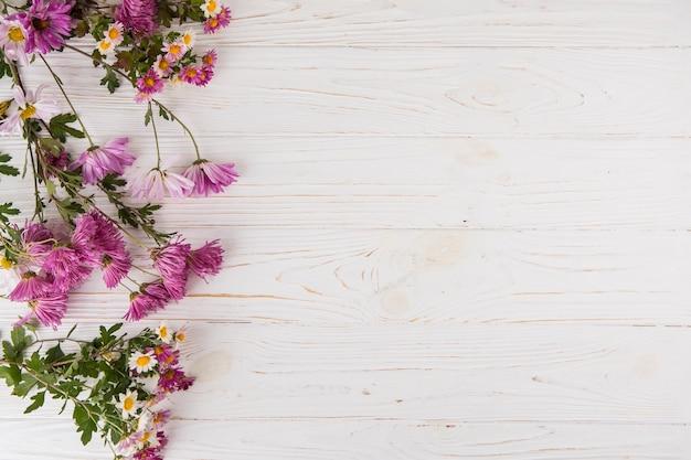 Разные яркие цветы разбросаны по светлому столу