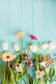Different bright flowers scattered on table