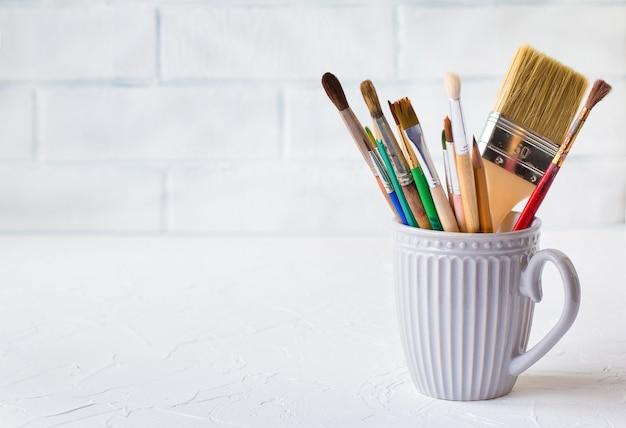レンガの壁の背景に白いテーブルの上の灰色のマグカップのさまざまなブラシ