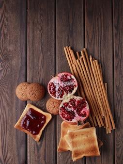 Различные булочки из свежего хлеба и колоски пшеницы на коричневом фоне старинных