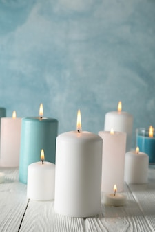Different burning candles against blue, space for text