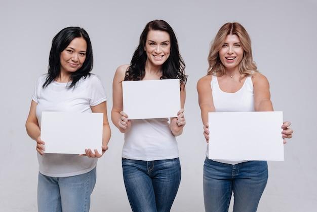 異なるが団結。シンプルな服を着てポーズをとっている間白い看板を保持している壮大なアクティブな強い女性