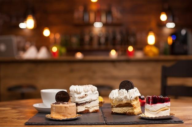 コーヒーショップの木製テーブルにプリンクリームとさまざまなケーキ。新鮮な赤い果物を上に乗せたプリンケーキ。おいしい一杯のコーヒー。