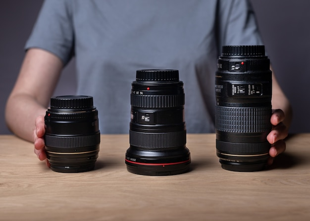 Different camera lenses on wooden table. 85 mm, 35 mm and 300 mm. various modern digital lenses of diverse sizes.