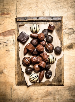 Different candy chocolates on old paper. on wooden background.
