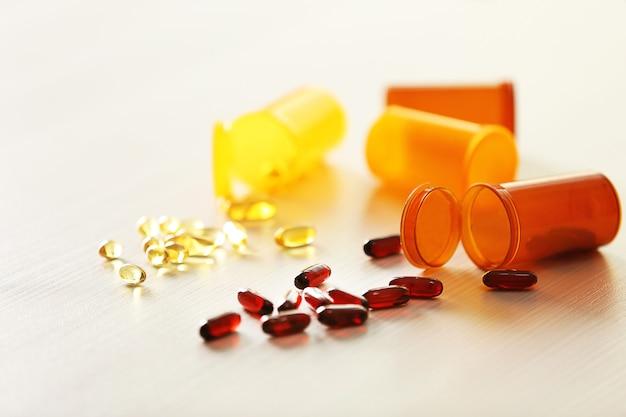 Различные капсулы пролились из бутылок апельсиновых таблеток на деревянный стол, крупным планом