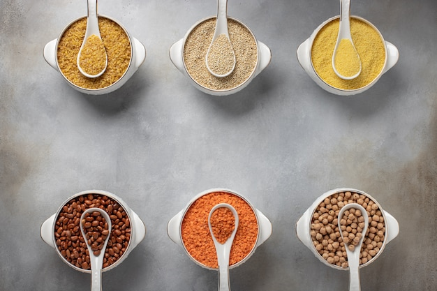 Different cereals in bowls (couscous, beans, quinoa, bulgur, lentils, chickpeas) healthy food,