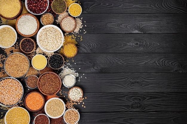 ボウルにさまざまなシリアル、穀物、種子、ひき割り穀物、マメ科植物、豆、コピースペースのある黒い木製の背景に生のお粥コレクションの上面図