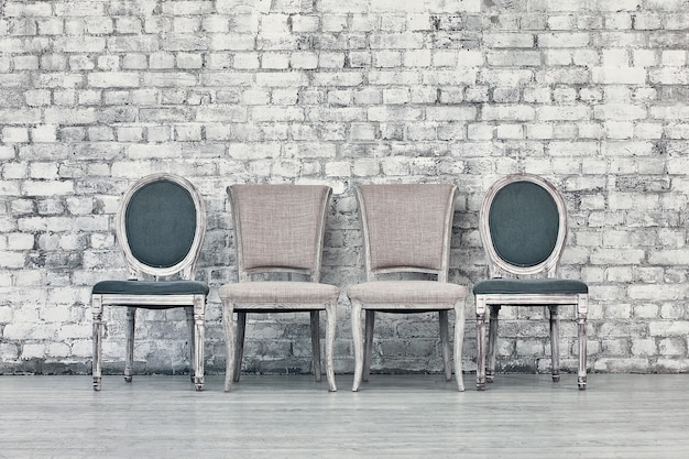 Different chairs in a line against a white brick wall