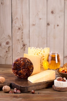 Different cheese classic choice, on an old wooden board and nuts. different cheese on an old wooden board. dutch cheese and beer