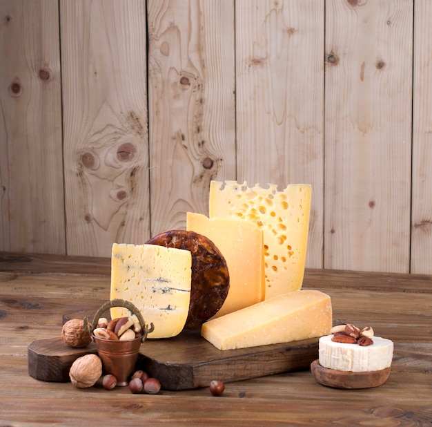 Different cheese classic choice, on an old wooden board and nuts