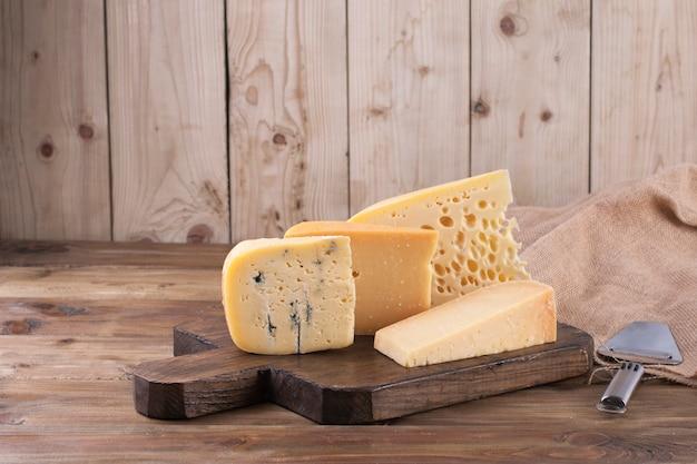 Классический выбор различных сыров, на старой деревянной доске, нож для сыра и ткань