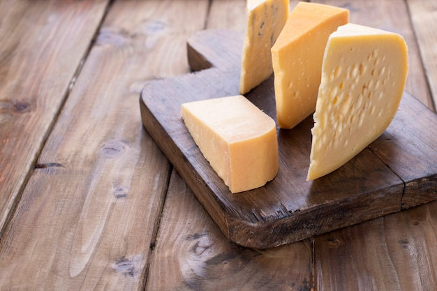 Different cheese on an old wooden board. dutch cheese