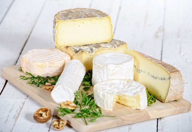 Different cheese with walnuts on a white wooden board