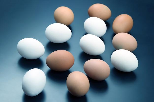 Различные куриные яйца лежат на темном фоне. здоровое и витаминное питание