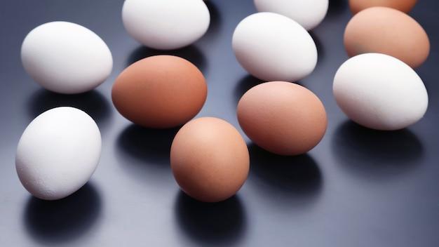 Различные куриные яйца лежат на темном фоне. сырая пища для приготовления