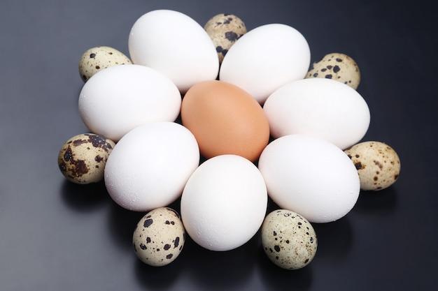 さまざまな鶏卵が暗闇にランダムに横たわっています