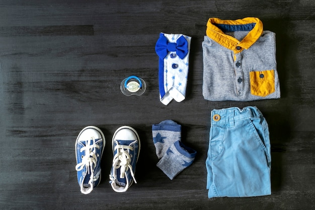 Different child clothes, pants, shirt, accessories on black wooden table with copy space, flat lay. baby shower, stuff, boy birthday, newborn party