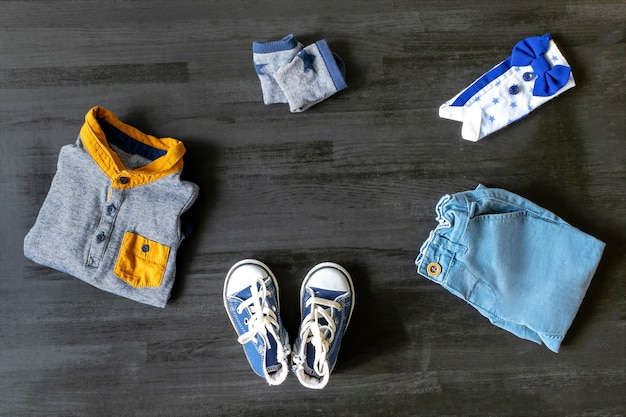 Different child clothes, shoes, sneakers, pants, accessories on black wooden table with copy space, flat lay. baby shower, stuff, present for boy birthday, newborn party