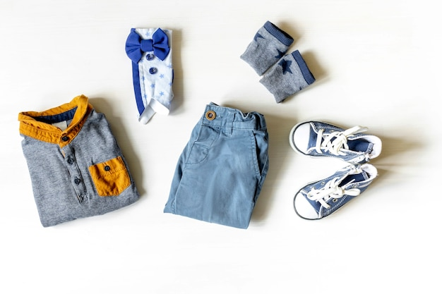 Different child clothes, shoes, sneakers, pants, accessories on white table with copy space, flat lay. baby shower, decorations, stuff, present for boy birthday, newborn party.