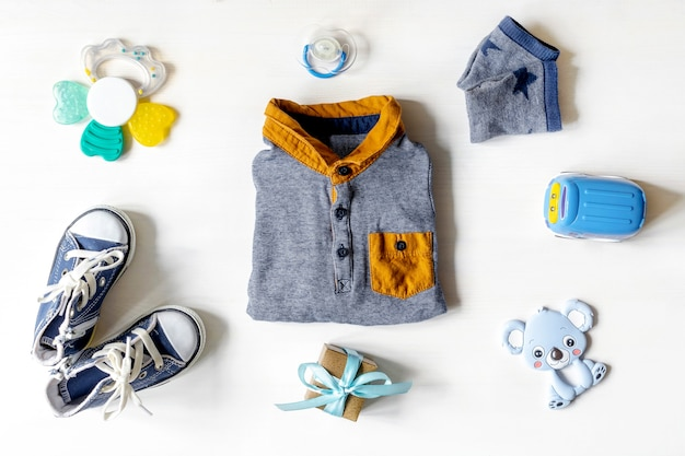 Different child toys, clothes, accessories, gift box on white table with copy space, flat lay. baby shower, decorations, stuff, present for boy girl first year birthday, newborn party