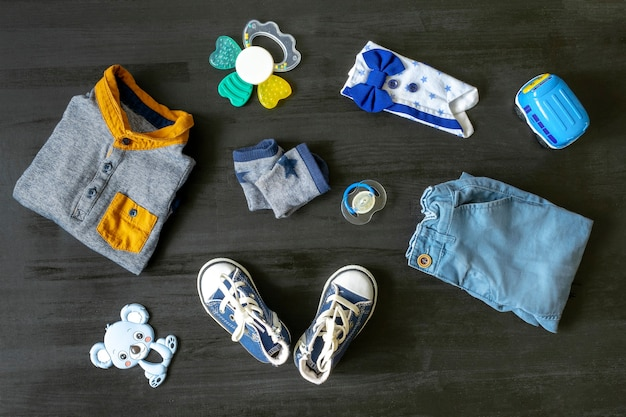 Different child toys, clothes, sneakers on black woosen table with copy space, flat lay. baby shower, accessories, decorations, stuff, present for boy girl first year birthday, newborn party