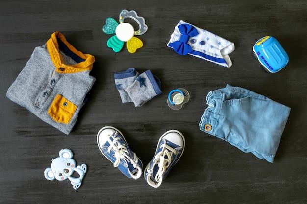 Различные детские игрушки, одежда, кроссовки на черном woosen столе с копией пространства, плоская планировка. детский душ, аксессуары, украшения, прочее, подарок мальчику и девочке на первый год рождения, вечеринка для новорожденных
