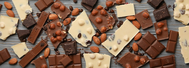 Different chocolate on gray wooden background, top view