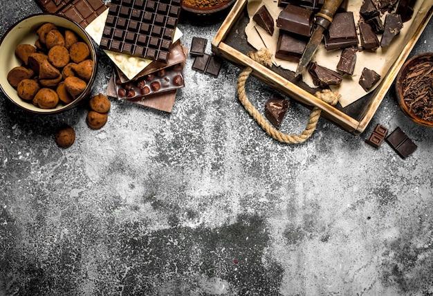 Различный шоколад с трюфелями на деревенском фоне