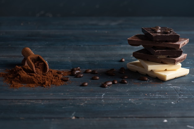 Different chocolates, coffee bean and  ground coffee on wooden background