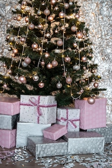 Different christmas gift boxes on floor under fir tree
